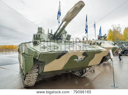 Nizhniy Tagil, Russia - September 27. 2013: Visitors examine military equipment on exhibition range. Airborne tracked armoured personnel carrier BMD-4M with additional protection poster