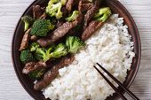 beef with broccoli and rice on a plate on the table close-up. horizontal view from above poster