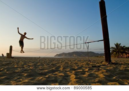 Unidentified man balancing on slackline at a beach in Manabi, Ecuador