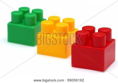 Red lego piece in focus green and yellow not in focus.Isolated on white background poster