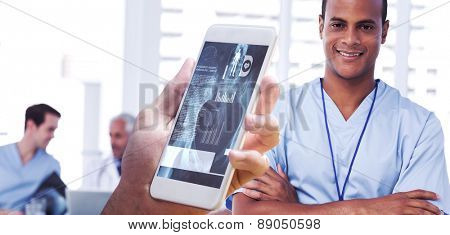 hand holding smartphone against smiling doctor with arms crossed
