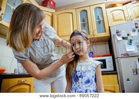 Mom makes daughter hairstyle in the kithen before school