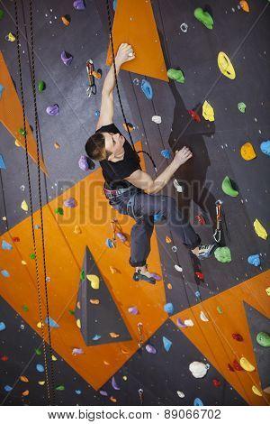 Man practicing top rope climbing in climbing gym