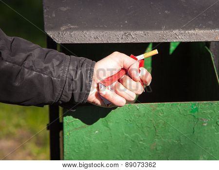 Man's Hand Breaks A Pack Of Cigarettes