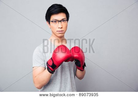 Young asian man in glasses standing in boxing gloves over gray background