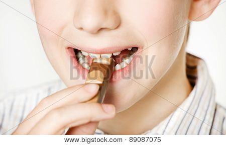 Smiling boy eating milk chocolate bar