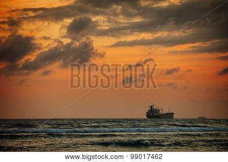 Enormous Tanker Ship On The Horizon At Sunset