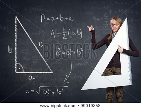 female student with a big ruler pointing at  Pythagorean theorem on blackboard