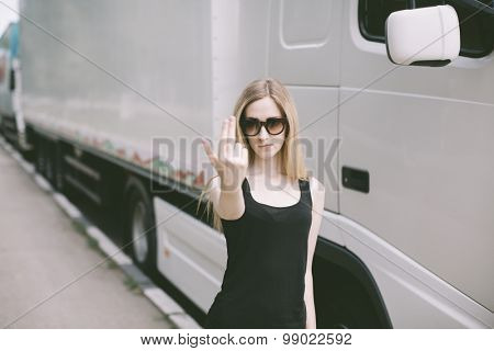 young woman with sunglasses near white cargo truck showing index and middle fingers
