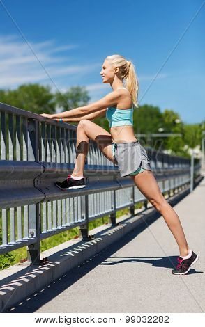 fitness, sport, exercising and healthy lifestyle concept - smiling woman stretching leg outdoors