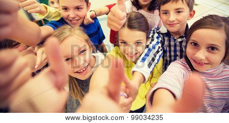 education, elementary school, learning, gesture and people concept - group of school kids and showing thumbs up in classroom