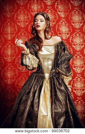Beautiful young lady in the lush expensive dress posing over vintage background. Renaissance. Barocco. Fashion.