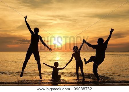 Silhouette Of Happy Family Who Playing On The Beach At The Sunset Time.