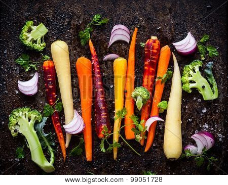 raw rainbow carrot , broccoli and onion for roasting, on a baking tray