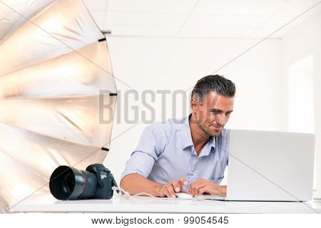 Portrait of a happy photographer using laptop at his workplace