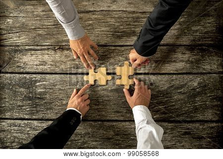 Four Successful Business Men Joining Two Puzzle Pieces Each Being Held By Two Partners