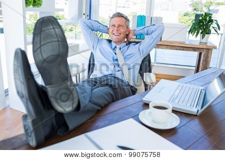 Businessman relaxing in a swivel chair in office