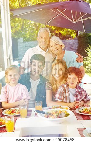 Happy vegan family with grandparents at lunch in summer