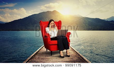 tired businesswoman sitting on the red chair on wood moorage over beautiful landscape