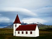 Typical red-roofed white little church in Hellnar (Iceland). Behind it can be seen the Snaefellsjokull volcano. poster