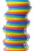 Pile of rainbow colored plastic plates on white background poster