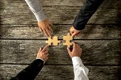 Four successful business men joining two puzzle pieces each being held by two partners rustic wooden background. Conceptual of merger or creative cooperation of two business companies. poster