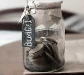budget concept chalk inscription glass bank with many world coins and budget word or label on saving money jar poster