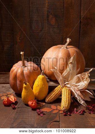 Autumn still life - pumpkins, leaves and physalis against the background of old wooden wall.