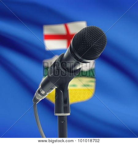 Microphone On Stand With Canadian Province Flag On Background - Alberta