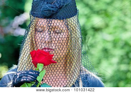 a young, grieving widow with veil and rose. death and inheritance.
