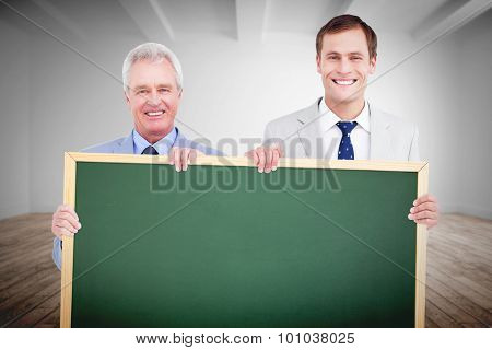 Smiling tradesmen holding blank sign against digital room