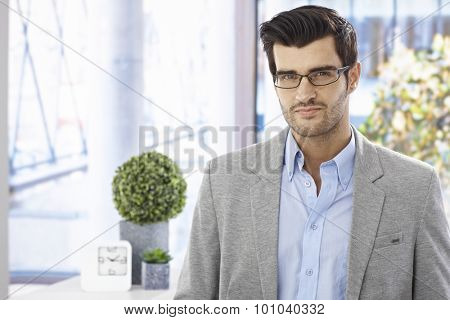 Portrait of goodlooking young businessman in glasses, looking at camera.