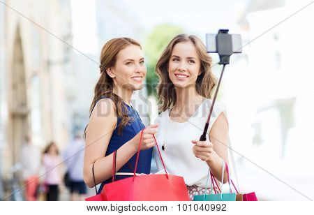sale, consumerism, technology and people concept - happy young women with shopping bags and smartphone selfie stick taking picture on city street