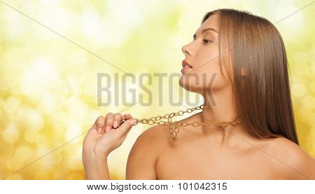 beauty, luxury, people, holidays and jewelry concept - beautiful woman wearing golden necklace or chainlet over yellow lights background