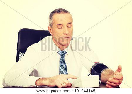 Mature businessman measuring blood pressure.