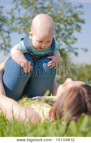Mom Makes The Charge With Your Baby On The Grass