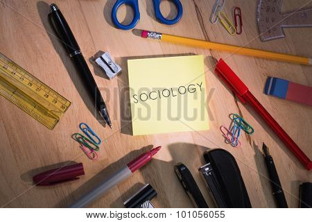 The word sociology against students table with school supplies