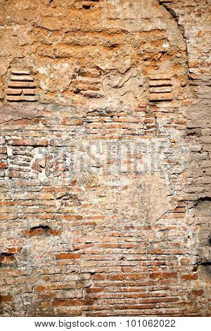 Ancient weathered brick wall background texture with exposed red clay bricks and missing plaster on a historical building