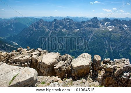 Scenic Overview of Allgau Alps Mountain Range Scenery Stretching into Distance from Rocky Observation Point on Sunny Day with Blue Sky