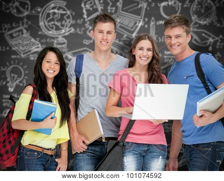 A smiling group of students holding a laptop while looking at the camera against black background