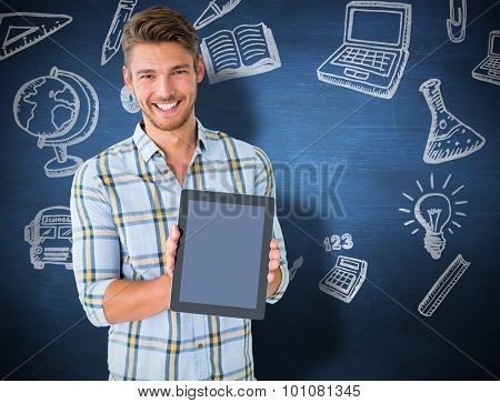 Young student showing tablet pc against blue chalkboard