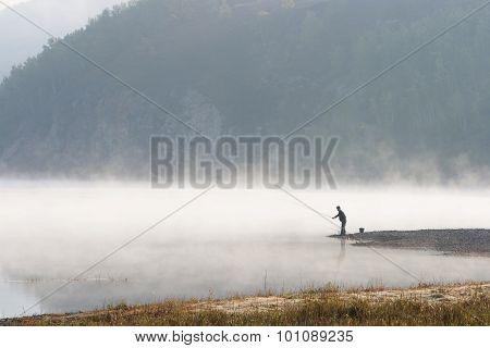 Man Fishing At River Shore