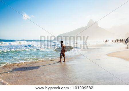 RIO DE JANEIRO, BRAZIL - APRIL 24, 2015: Brazilian surfer walking with surfboard toward Two Brothers Mountain at Ipanema Beach on April 24, 2015 at Copacabana Beach, Rio de Janeiro. Brazil.
