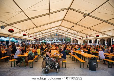 BARCELONA, SPAIN - MAY 02: View of a Bavarian styled Oktoberfest in Barcelona, Spain taking place in an undercover marquis with rows of benches and people. May 02, 2015.