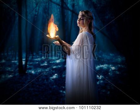 Young elven girl with fire in night forest