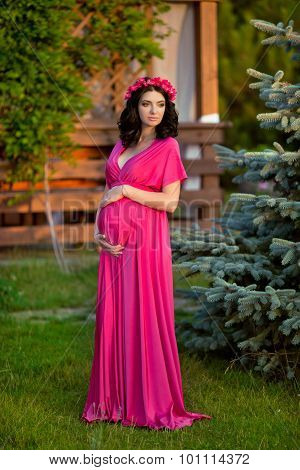 Beautiful Pregnant Woman Touching Her Belly Wearing In Pink Dress And Flowers Chaplet On Head. Attra
