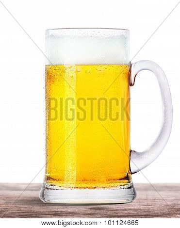 Frosty beer with foam isolated on wooden table