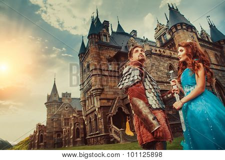 Beautiful Princess Is Giving Sword To Her Bravel Knight. Ancient Castle On The Background.