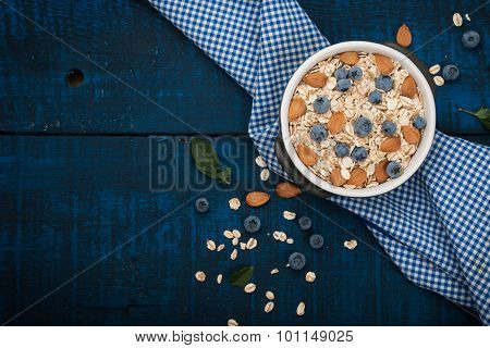 A healthy breakfast on a dark blue wooden background: Oatmeal, milk, blueberries, honey and almonds.