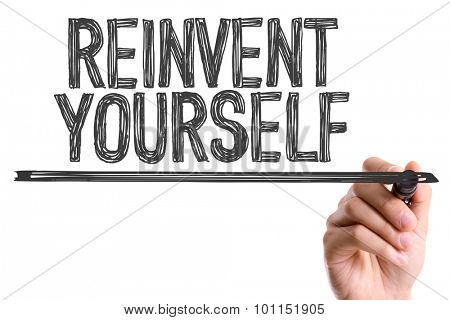 Hand with marker writing the word Reinvent Yourself